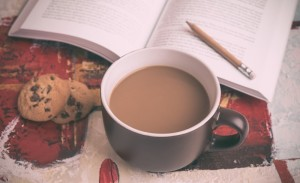 coffee-cup-and-cookies-on-table-with-book-in-background