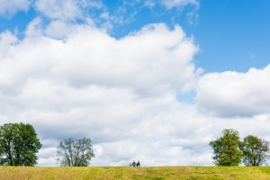 distant-view-of-couple-sitting-on-bench-in-meadow